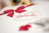 коробку Raffaello перевязанную красной атласной ленточкой